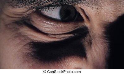 Evil man's eye in the dark