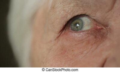 Eye of old woman at home - Sad eyes of senior woman