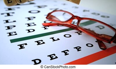 Eye test dice falling onto eye test with red reading glasses...