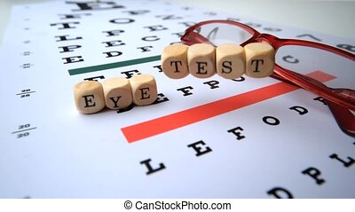Eye test dice falling onto eye test with reading glasses in...