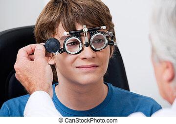 Eye Test Through Trial Frames - Optometrist taking eye test...
