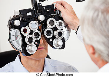 Eye Test With the Phoropter - Optometrist performing eye...
