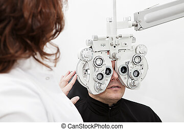 eye testing device - man being sight tested by the...