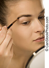 closeup of woman shaping her eyebrows with brush