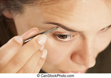 Young beautiful woman pluck her eyebrows with tweezers