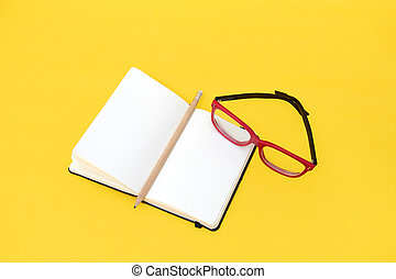 Eyeglasses and notebook isolated on yellow background