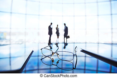 Eyeglasses and touchpads at workplace with businesspeople ...