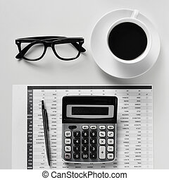 eyeglasses, coffee and calculator on an office desk