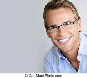 Young handsome man with great smile wearing fashion eyeglasses against neutral background with lots of copy space
