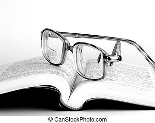 Eyeglasses on a book. Black and white on a white bagground....
