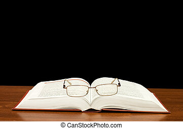 Eyeglasses on books on a wooden table