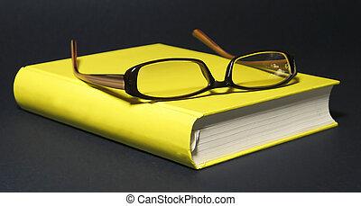 Eyeglasses on the yellow book