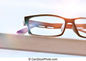 Eyeglasses on wood table and blue background front close up