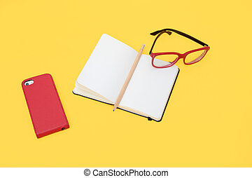 Eyeglasses, smartphone and notebook isolated on yellow background