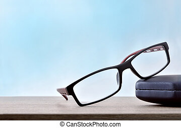 Eyeglasses with case on wood table blue background