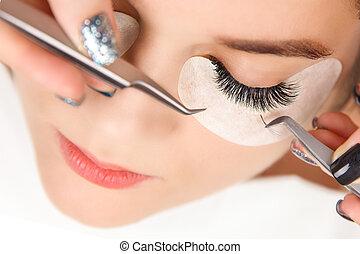 Eyelash Extension Procedure. Woman Eye with Long Eyelashes. Close up, selective focus.