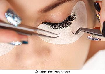 Eyelash Extension Procedure. Woman Eye with Long Eyelashes....