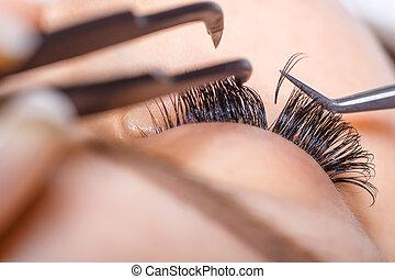 Eyelash Extension Procedure. Woman Eye with Long Eyelashes. Lashes. Close up, macro, selective focus