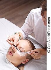 Eyelash Extension Procedure. Woman Eye with Long Eyelashes. Lashes, close up, selected focus.