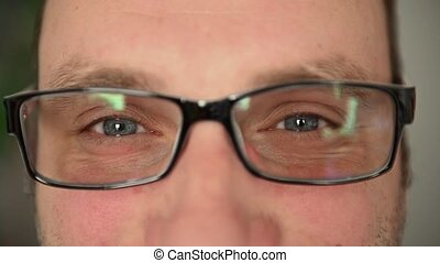 Eyes of a man in glasses close-up. There are emotions on the face. Facial muscles. Portrait of happy guy with eyeglasses looking at camera. Close up of a joyful man with beard looking at camera.
