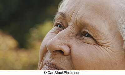 Eyes of elderly woman in the park. looking up in the sky. Extreme close up