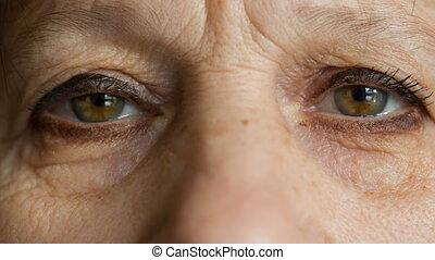 Eyes of elderly women look at camera - Eyes of elderly woman...