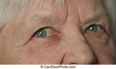 Eyes of old woman looking straight - Sad eyes of senior...