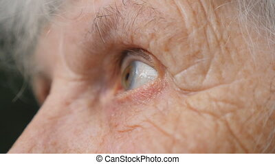 Eyes of old woman looking up and then moving from side to side. Eyes of an elderly lady with wrinkles around them. Close up Side view Slow motion