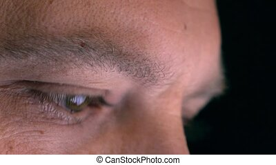 Eyes of serious caucasian man using his tablet computer, profile view. Screen reflecting in the eyes, device lighting glow. 4K extreme close up shot