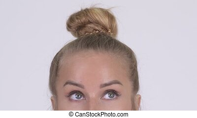 Eyes of young blonde woman thinking against white background...