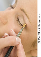 A beautiful young woman having her eyeshadow applied by a beautician