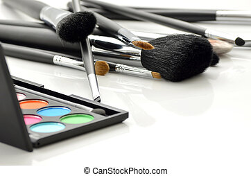 Professional makeup brushes and eye-shadows palette on white background.
