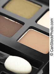Eye shadows of natural colors and applicator close-up in black container.