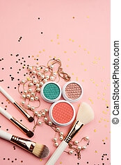Eyeshadows and makeup brushes on a pink background Copy Space top view