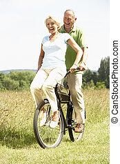 fälliges ehepaar, fahrenden fahrrad, in, landschaft