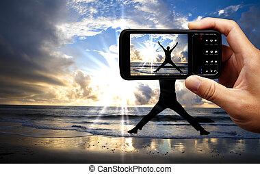 fényképezőgép, mobile telefon, és, boldog, ugrás, ember, a parton, -ban, gyönyörű, napkelte
