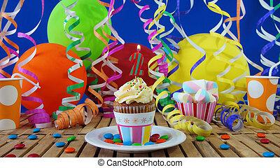 födelsedag, cupcake, med, vaxljus brännande, på, rustik, trä tabell, med, bakgrund, av, färgrika ballonger, plast kopp, och, candies, med, blå vägg, in, den, bakgrund