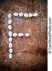 'F' alphabet made form white stone
