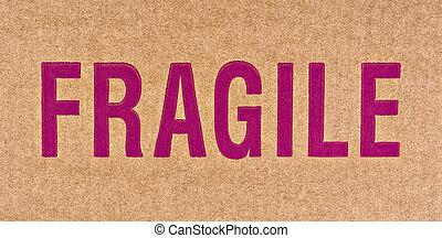 F-R-A-G-I-L-E - The word FRAGILE in red on a brown cardboard...