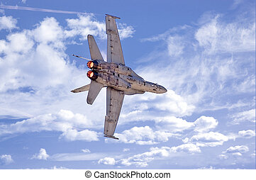 F18 Banking - An F-18 Hornet making a banking turn against a...