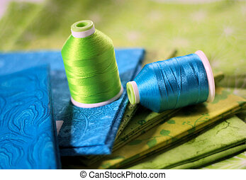 Blue and bright green fabric and thread ready for a sewing or quilting project.
