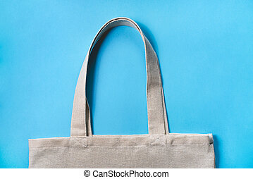 Fabric eco-bag on blue background. Flat lay, close up.