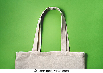 Fabric eco-bag on green background. Flat lay, close up.