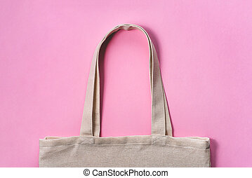 Fabric eco-bag on pink background. Flat lay, close up.