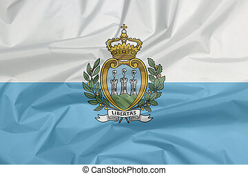 Fabric flag of San marino. Crease of Sanmarinese flag background, a horizontal bicolour of white and light blue; charged with the Coat of arms.