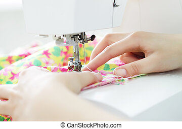 Fabric in a sewing machine on a light background