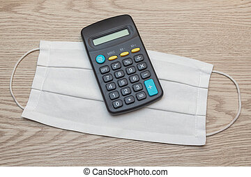 Fabric mask and calculator on wooden background