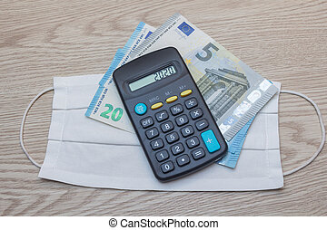 Fabric mask, banknotes and calculator as concept for the price of protection against coronavirus