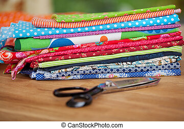 Pile of colorful fabric samples and scissors