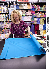 fabric store girl - girl cutting fabric in a fabric store